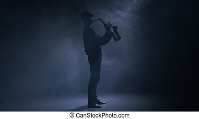 In a dark smoky studio man playing the saxophone - In a dark...