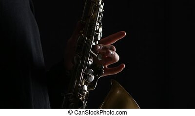 Man's fingers playing on the saxophone beautiful blues...
