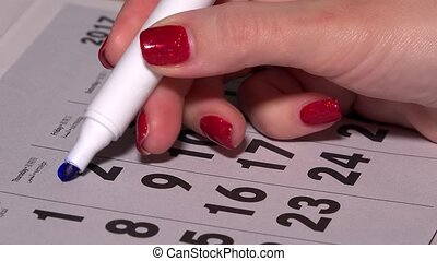 Woman hand circle and cross days on paper calendar. Planning...