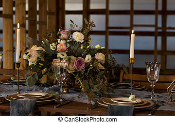 Laid Table By wedding banquet in a wooden barn. Candles and...