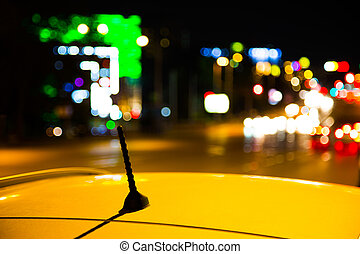 Roof of a yellow taxi cab in city at night