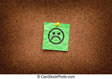 Green paper note with sad face on a cork board. Depression...
