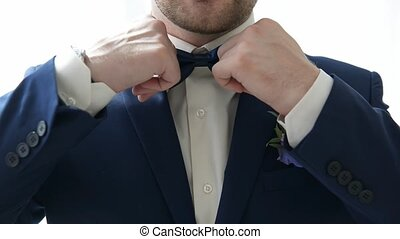 man straightens his tie indoor