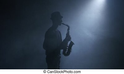 Saxophone. Man musician playing an instrument in a smoky...
