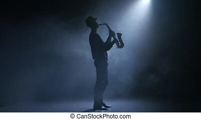 In the spotlight musician man playing the saxophone. Smoky...