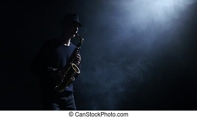 Silhouette the men musician improvising on the saxophone....