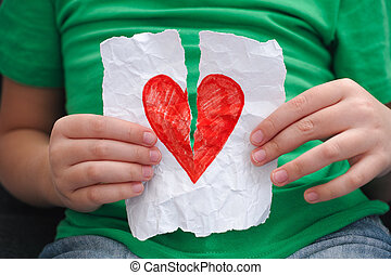 Child ripping red heart on a piece of paper