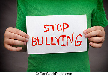 Stop Bullying - A young boy holds Stop bullying sign.