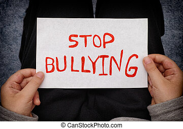 A young boy holds Stop bullying sign. Close up.