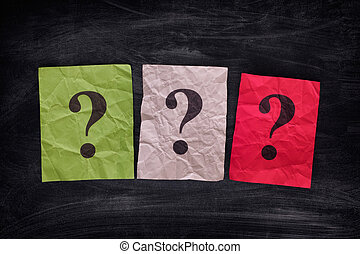 Colorful paper notes with question marks on black board....