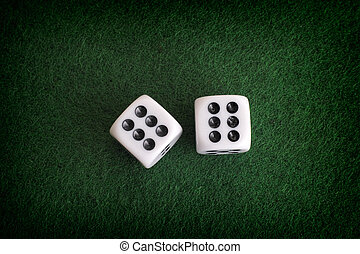 Two dices on a green background. Close up.