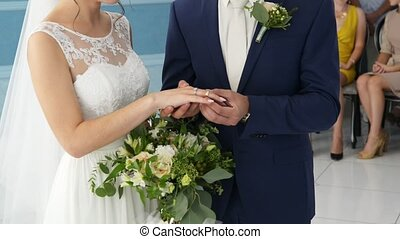 closeup of bride and groom exchanging wedding rings indoor