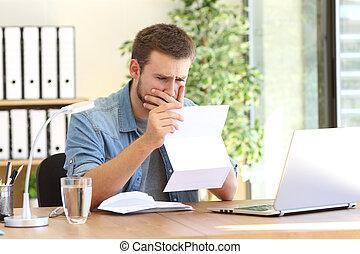 Worried entrepreneur reading a letter