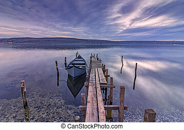 exciting long exposure landscape on a lake with wooden pier and boat .