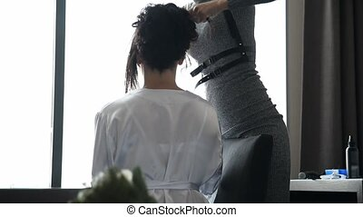 Hairdresser is finishing hairstyle for bride