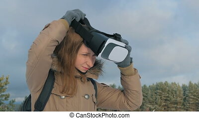 Woman putting on and using virtual reality glasses in winter...