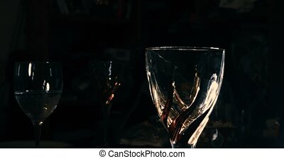 Waiter pouring red wine on wine-glass in dark room retro...