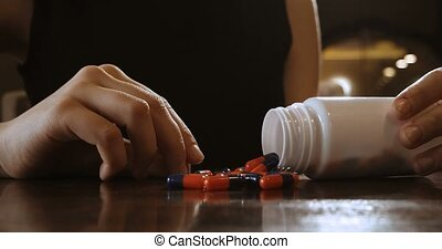 Orange and blue color pills spilled out of bottle on...