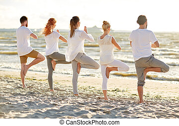 group of people making yoga in tree pose on beach - yoga,...