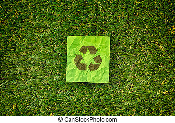 Recycle symbol laying on a green grass