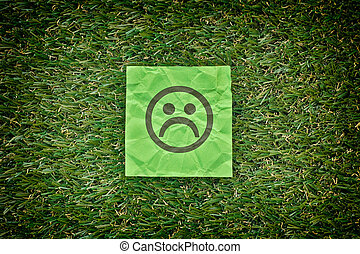 Green paper with sad unhappy face on a green grass. Close...