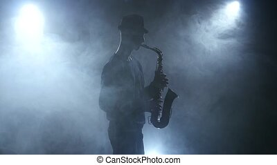 Slow play jazz music on saxophone on dark smoky studio, man...