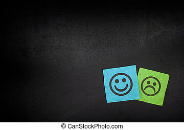 Blue and green paper notes with happy and sad faces on...