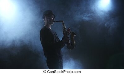 On dark smoky studio improvisation jazz music on saxophone,...