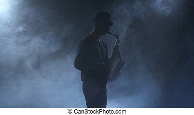 Young jazzman plays the sax. Dark smoky studio with...