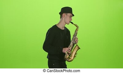 Saxophonist playing on the gold musical instrument. Green...