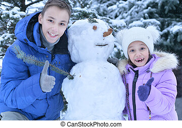brother and sister making a snowman