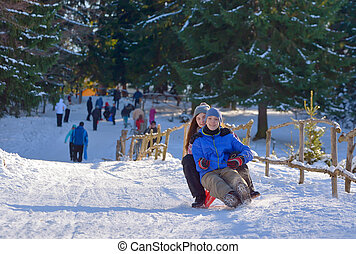 Teenagers slide downhill in wintertime