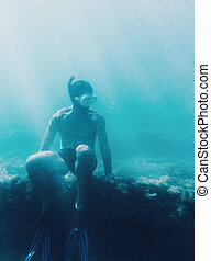 Free diver sitting on reef - Underwater image of young man...