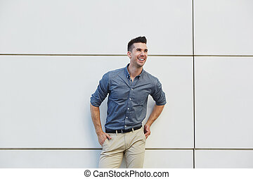 laughing friendly business man standing by white wall -...