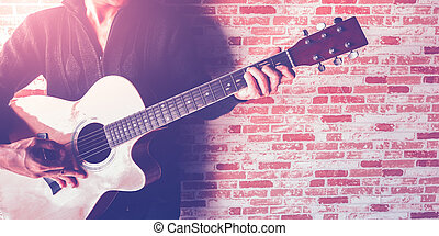 guitar - A man playing guitar on brick wall with croped...