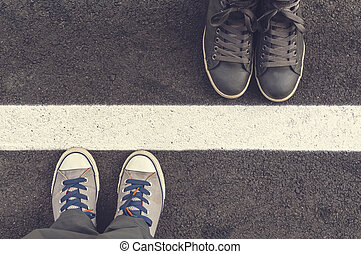 Two pair of sneakers on a asphapt road. Top of view.