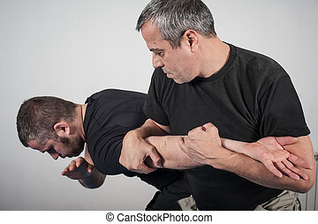 Kapap instructor demonstrates arm bar techniques with his...