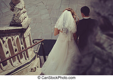 Newlyweds go down old stone stairs