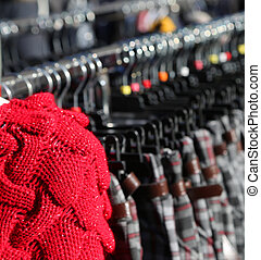 Red sweater wool and many winter clothes on hangers