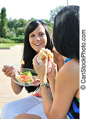 Friends having great time when eating outdoors - Two friends...