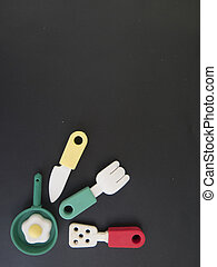 Background of eating utensils with a toy and scrambled eggs