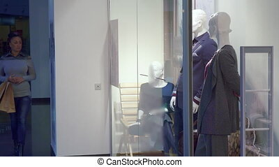 Woman comes to the store window at the mall - Attractive...