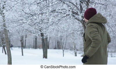 man throws off snow from tree branches in park - man throws...