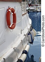 white boat side with fender and round lifesaver - white boat...