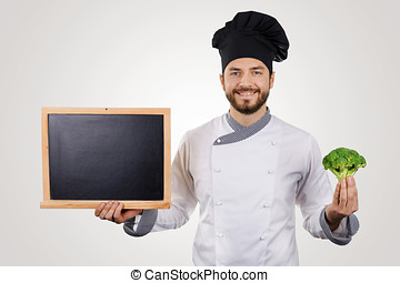 smiling young chef with blank blackboard and broccoli in hand