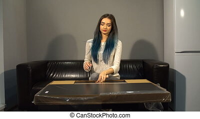 Young cute girl with colored hair sitting on a couch in their new apartment to put together a table. Shoot in kitchen. Demonstrates content.