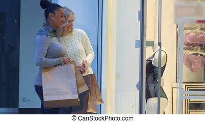 Women look at underwear through the store window - Two young...