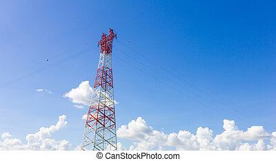 Telecommunication mast with microwave link and TV transmitter antennas on blue sky.