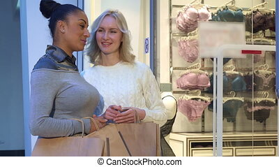 Women discuss bras and panties near the lingerie shop - Two...