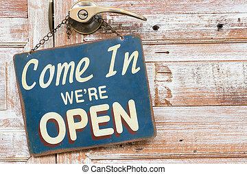 Come In We're Open on the wooden door, copyspace on the...